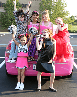 Six girls pose with a pink limo as part of a Sweet and Sassy birthday package